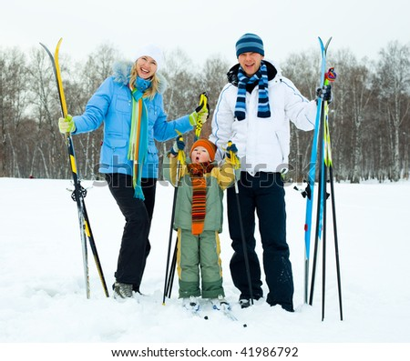 happy young couple going skiing with their son on a warm winter day