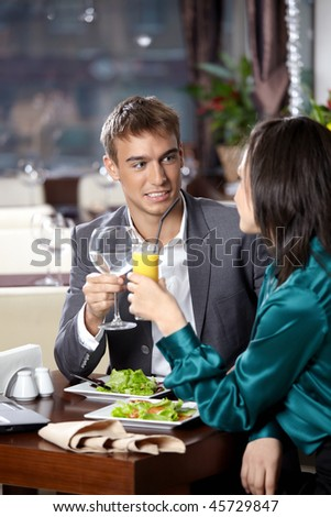 Happy young couple has dinner at restaurant - stock photo
