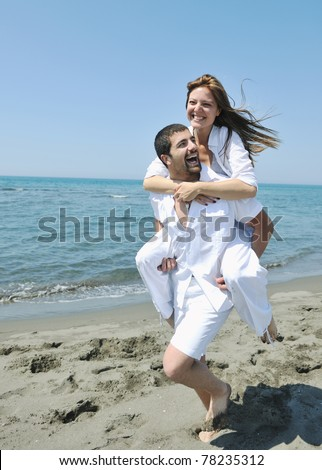 happy young couple have fun and romantic moments on beach at summer season and representing happynes and travel concept - stock photo