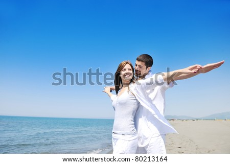happy young couple have fun and romantic moments on beach at summer season and representing happiness and travel concept - stock photo