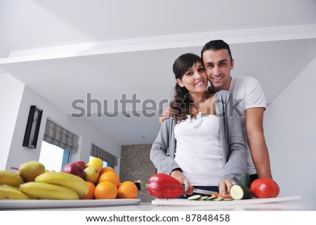 happy young couple have fun in  modern kitchen indoor  while preparing fresh fruits and vegetables food salad - stock photo