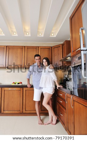 happy young couple have fun in modern wooden  kitchen indoor while preparing fresh food - stock photo