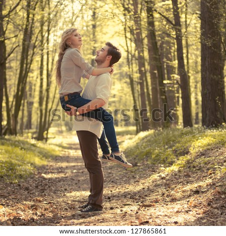 happy young couple have fun in the summer forest - stock photo