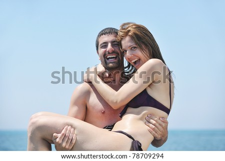 happy young couple have romantic time on beach at sunset