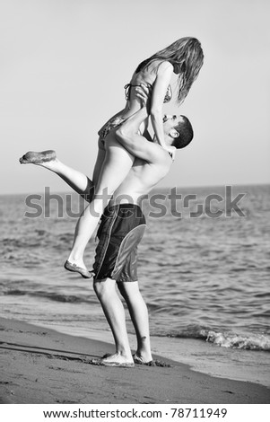 happy young couple have romantic time on beach at sunset - stock photo