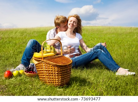 happy young couple having a picnic outdoor on a summer day