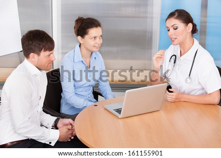 Happy Young Couple Having Appointment With Female Doctor At Clinic - stock photo