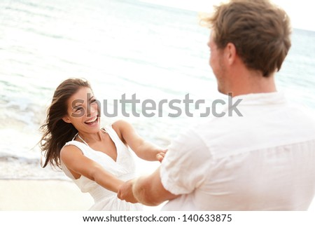 Happy young couple having beach fun on vacation travel holidays. Asian woman and man playing playful enjoying love on date or honeymoon. Multiracial couple in their 20s. - stock photo