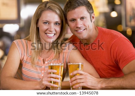 Happy young couple having beers at a bar - stock photo
