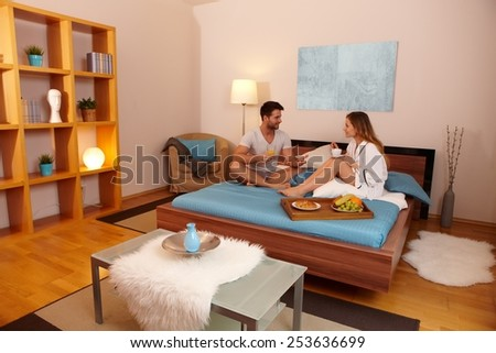 Happy young couple having breakfast in bed. - stock photo