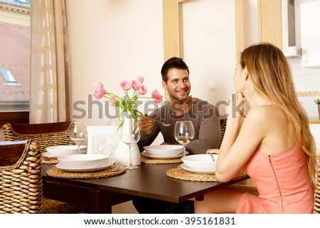 Happy young couple having dinner at home, smiling. - stock photo