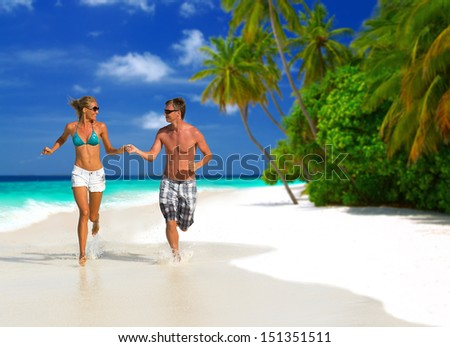 Happy young couple having fun, holding hands, looking at each other, running on the beach, having tropical vacation on Maldives - stock photo