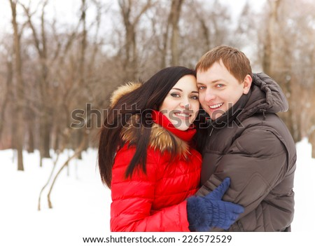 Happy young couple having fun in the winter park