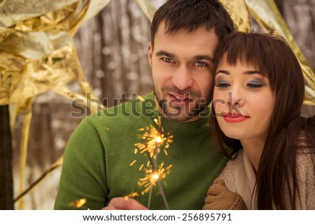 Happy young couple having fun in winter park - stock photo