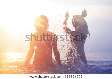 happy young couple having fun, man and woman in the sea on the beach. vintage retro style with soft focus and sun flare - stock photo
