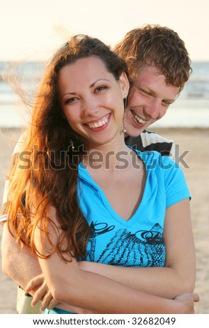 happy young couple having fun on sea cost - stock photo