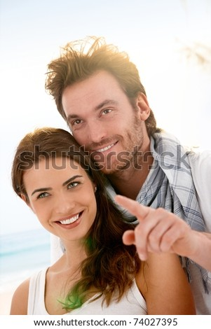 Happy young couple having fun on summer beach, looking away, smiling.? - stock photo