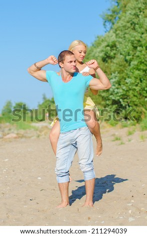 Happy young couple having fun on the beach. - stock photo