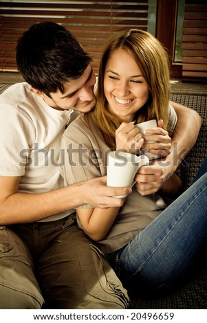 Happy young couple having fun on the sofa - stock photo