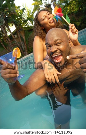 Happy young couple having fun outside in the pool