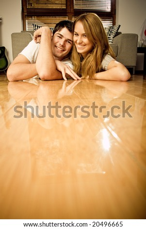 Happy young couple having on the floor - stock photo
