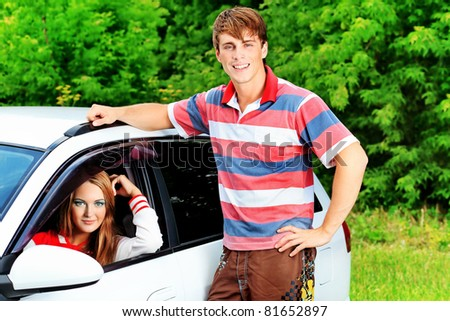 Happy young couple having summer trip on a car.
