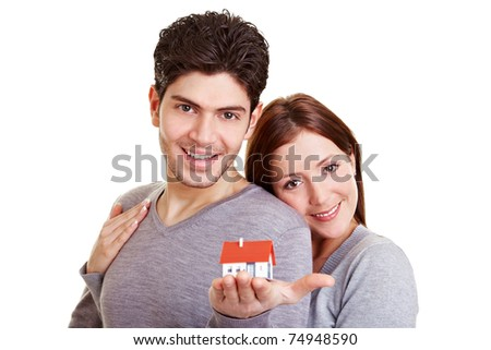 Happy young couple holding a miniature house in their hand - stock photo