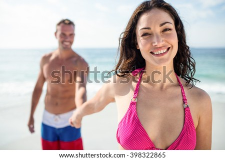 Happy young couple holding hand on the beach on a sunny day - stock photo