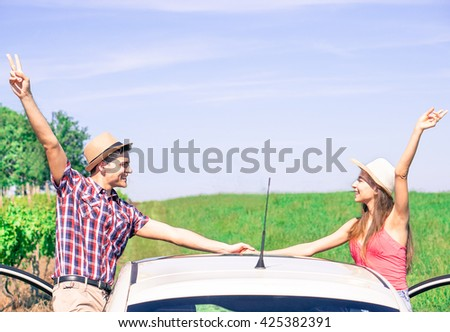 Happy young couple holding hands and having fun together outside of the car - Friends going on day trip in countryside - Concept of love and enjoying summer time - Warm saturated retro filter - stock photo