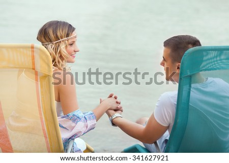 Happy young couple holding hands and looking at each other while sitting on sun beds on the beach - stock photo