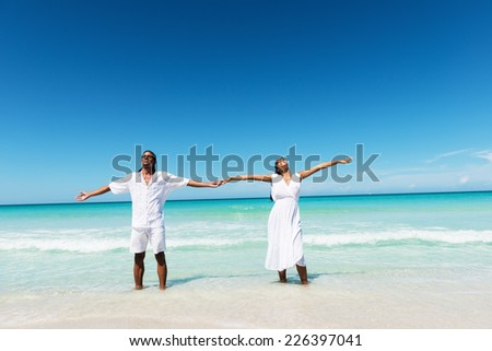 Happy, young couple holding hands at the tropical beach, arms outstretched.Copy space - stock photo
