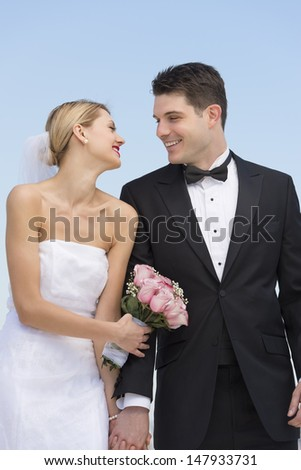 Happy young couple holding hands while looking at each other against clear blue sky - stock photo