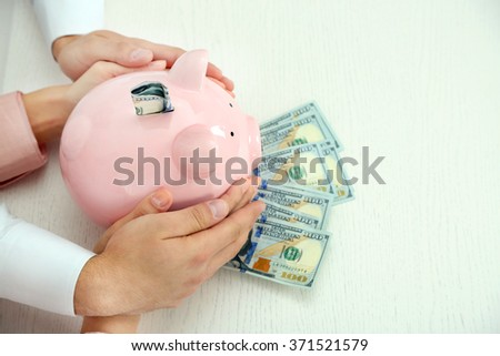 Happy young couple holding in hands piggy bank with dollar banknotes. Money savings concept - stock photo