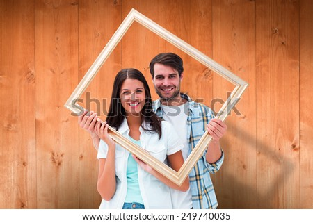 Happy young couple holding picture frame against wooden planks - stock photo