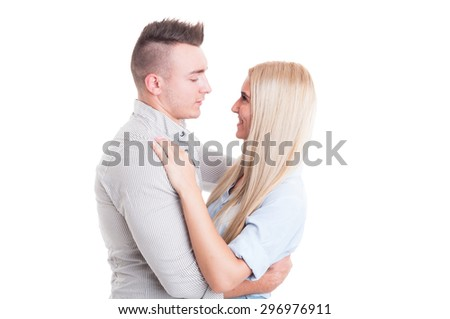 Happy young couple hugging and looking at each other or into eachother eyes - stock photo