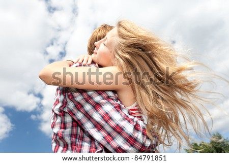 happy young couple hugging and smiling n sunny day - stock photo