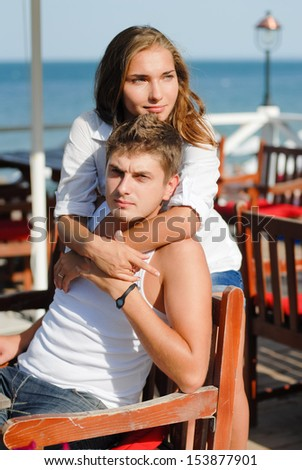 Happy young couple hugging each other at sea beach in summer outdoors - stock photo