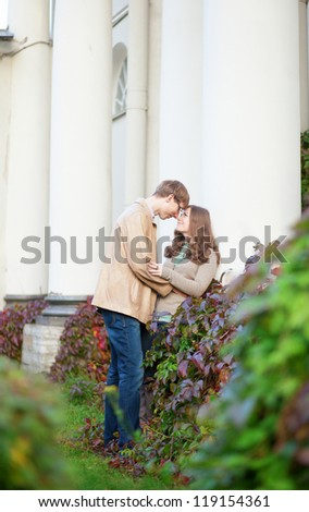 Happy young couple hugging in park - stock photo