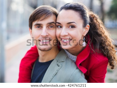 Happy young couple hugging in park at sunny spring day. Focus on women  - stock photo
