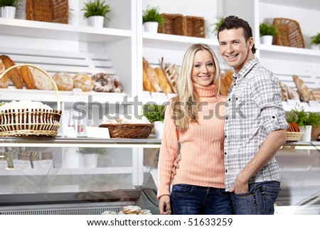 Happy young couple in a baker's shop - stock photo