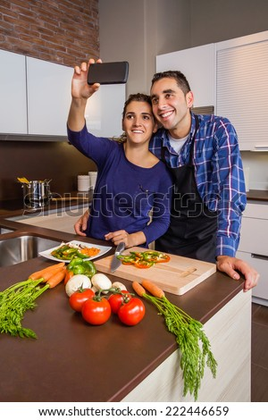 Happy young couple in a home kitchen taking a selfie with a smarphone while preparing healthy food. Modern family lifestyle concept. - stock photo