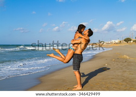 Happy young couple in bikini and shorts enjoying summer dusk at the beach, having fun walking barefoot, kissing and teasing one another.