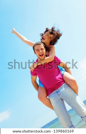 Happy young couple in casual cloths at the beach in sunny weather
