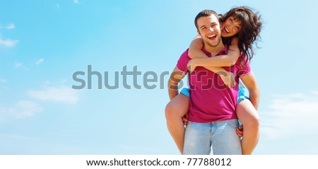 Happy young couple in casual cloths with a sky on background. Copyspace. - stock photo