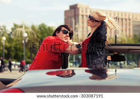 Happy young couple in convertible car - stock photo