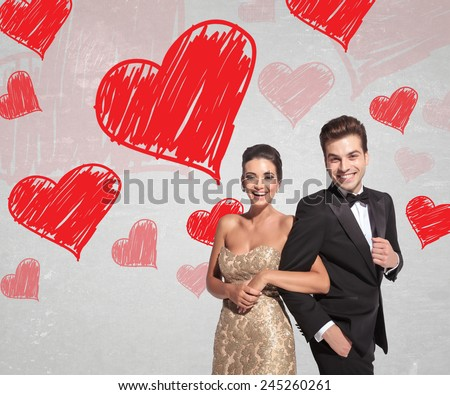 happy young couple in elegant tuxedo and dress laughing together while holding arms on hearts background - stock photo