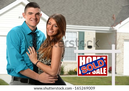 Happy young couple in front of newly sold home - stock photo