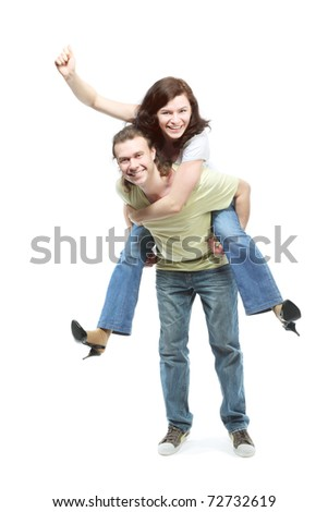 Happy young couple in jeans, funny girl jumps on boyfriend back - stock photo