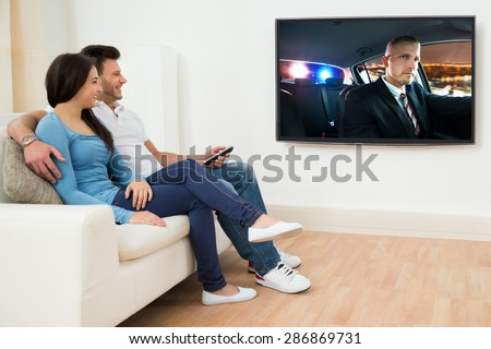 Happy Young Couple In Livingroom Sitting On Couch Watching Movie - stock photo