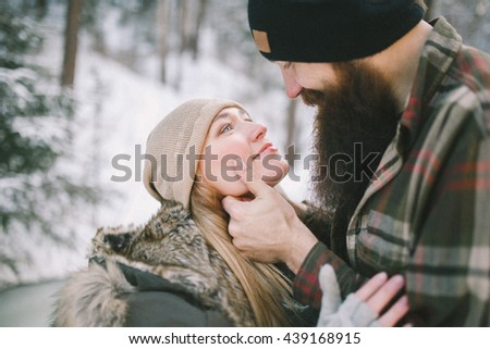 Happy young couple in love cuddling in rustic style in the winter forest. Close-up - stock photo